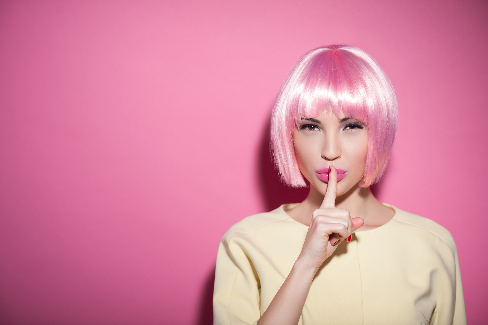 Save my secret. Portrait of attractive woman in a wig raising finger to her pink lips. She is standing and looking at camera mysteriously. Isolated and copy space in left side