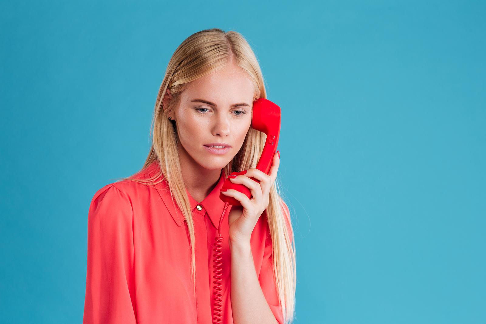 Sad blonde woman holding phone tube isolated on a blue background